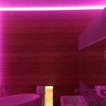 Das indirekte Beleuchtung der Naturholzwand im Bad kann dank RGB-Lichterkette in der Farbe angepasst werden